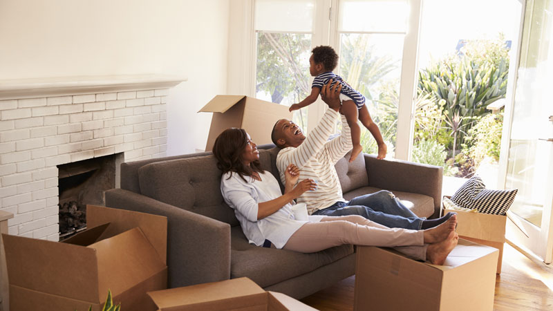happy smiling family of father and mother lounging at the couch with moving boxes on the ground lifting toddler baby over father's head