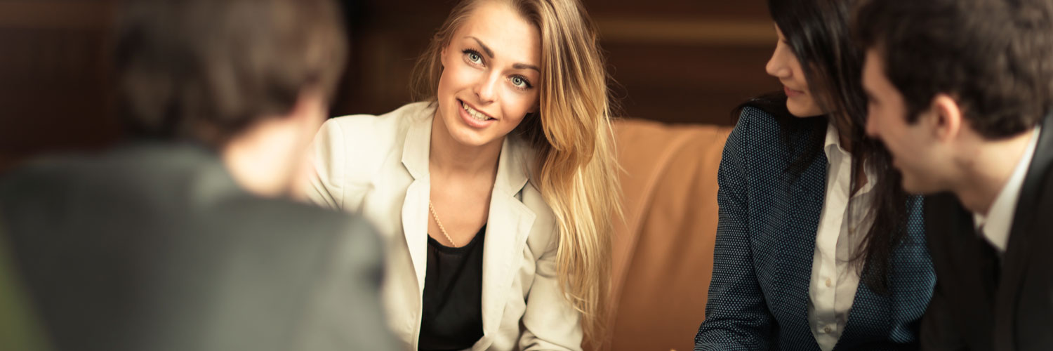 Professional woman in suit with long blonde hair having a meeting with coworkers