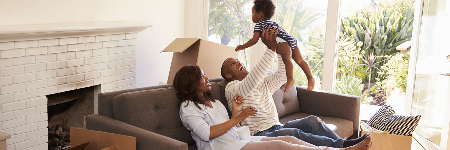 happy smiling family of father and mother lounging at the couch lifting toddler baby over father's head